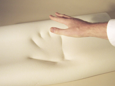 Hand touching memory foam mattress